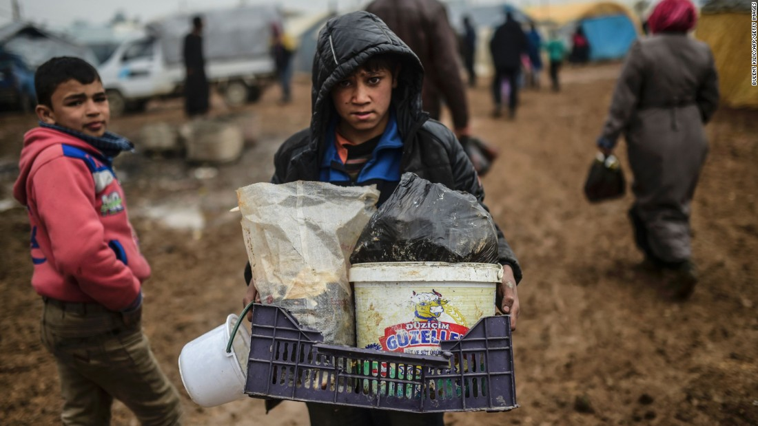 A child carries his belongings as Syrian refugees arrive at the Turkish border on February 6.
