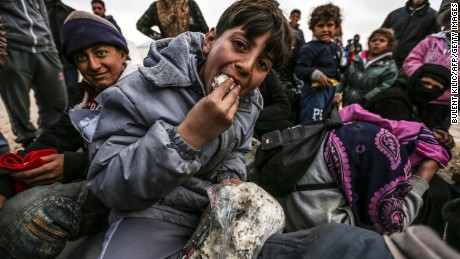 TOPSHOT - Syrian refugees are pictured in a camp as Syrians fleeing the northern embattled city of Aleppo wait on February 6, 2016 in Bab al-Salama, near the city of Azaz, northern Syria, near the Turkish border crossing. Turkey on Saturday said it was expecting a huge wave of Syrians fleeing a government onslaught on rebel-held territory, with a regional governor saying at least 70,000 people may be heading for the border. The United Nations said some 20,000 people had gathered at Syria's Bab al-Salam crossing with Turkey. An AFP reporter said the crossing was closed but the Syrian side of it was being supplied by aid trucks coming from Turkey.  / AFP / BULENT KILIC        (Photo credit should read BULENT KILIC/AFP/Getty Images)