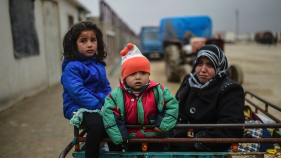 TOPSHOT - Refugee children arrive a the Turkish border crossing gate as Syrians fleeing the northern embattled city of Aleppo wait on February 6, 2016 in Bab al-Salama, near the city of Azaz, northern Syria. Thousands of Syrians were braving cold and rain at the Turkish border Saturday after fleeing a Russian-backed regime offensive on Aleppo that threatens a fresh humanitarian disaster in the country