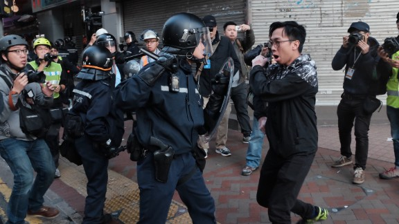 Riot police and a protester scuffle in a street in Mong Kok on February 9.