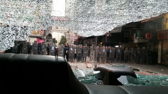 A view of riot police through the smashed windshield of a taxi, pictured on February 9.