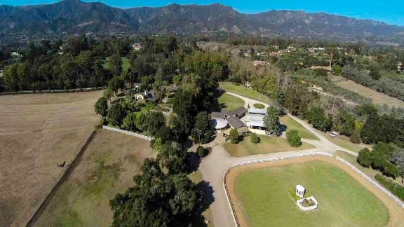 This drone aerial view shows the equestrian estate, including riding facilities, barn, and main residence, spread before the Santa Ynez Mountains.