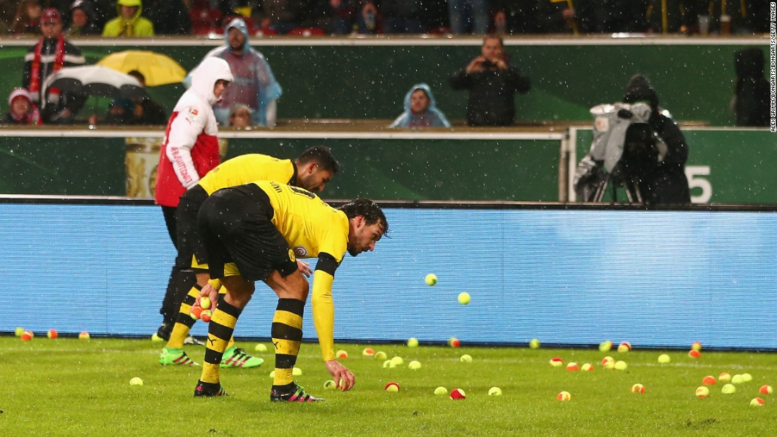 Borussia Dortmund players turned ball boys in the first half of their German Cup quarterfinal clash against Stuttgart Tuesday, after hundreds of fans threw tennis balls onto the pitch in protest at high ticket prices.