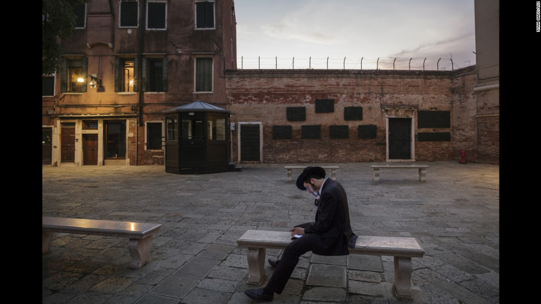 "A Jewish scholar reads in an empty courtyard in Italy's Venetian Ghetto. Jews were forced to live for centuries in this part of Venice, and it is where the modern-day word of ""ghetto"" was derived."