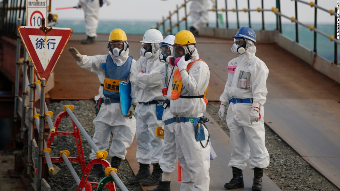 Workers, wearing protective suits and masks, stand near the No. 3 and No. 4 reactor buildings on February 10.