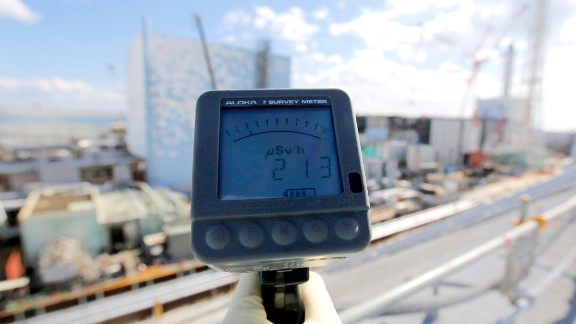 A TEPCO employee measures a radiation level of 213 microsieverts per hour in front of the No. 2, left, and No. 3 reactor buildings on February 10.