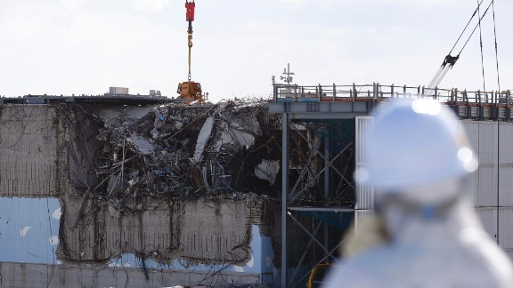 A member of the tour group, donning a protective suit and a mask, takes a look at the crippled No. 3 reactor on February 10.