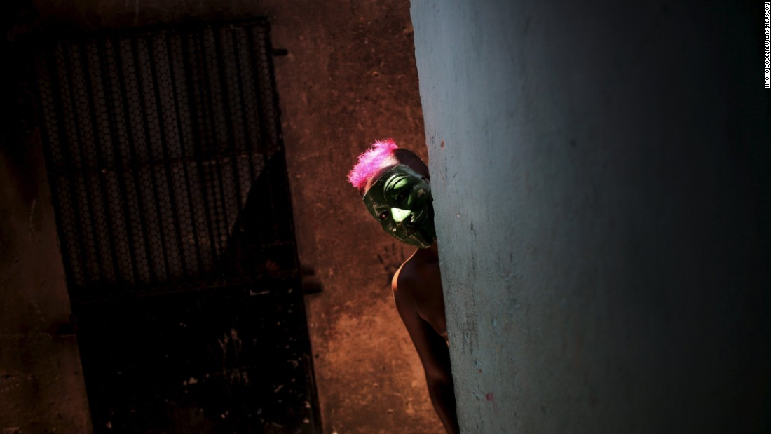 "A masked boy peeks around a corner during a <a href=""http://www.cnn.com/2016/02/05/world/gallery/carnival-2016/index.html"" target=""_blank"">Carnival</a> party in Recife, Brazil, on Sunday, February 7."