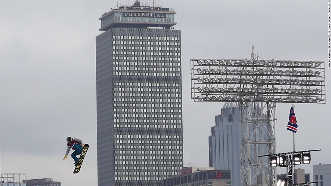 A snowboarder is captured making a jump with the high rise buildings of central Boston in the background.