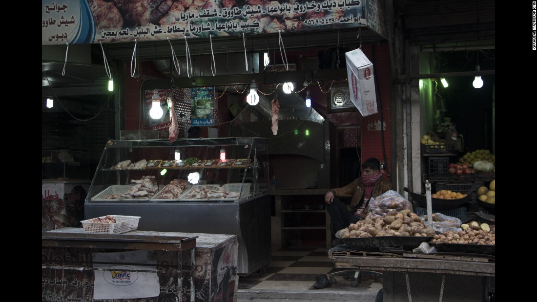 A stall holder waits for customers; there are reports of some hoarding of rice and flour as the regime's siege tightens.