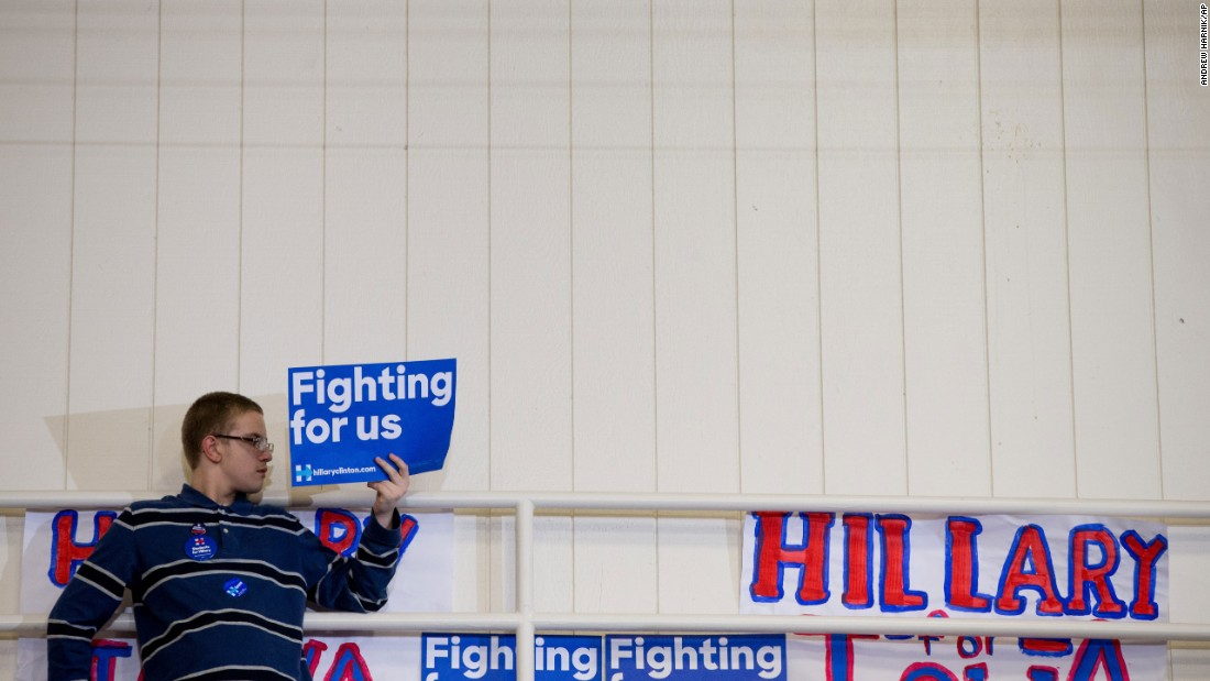 "Hillary Clinton has used the slogan, ""Hillary for America"" and also had supporters display posters saying ""Fighting for us."" A member of the audience holds a campaign sign at the top of a set of bleachers as Clinton speaks in Iowa on January 30."