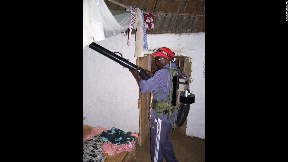 Research assistant Alassane aspirates mosquitoes inside a villager's home. After feeding on humans during the night, the mosquitoes often hide in bedding and along ceiling rafters.