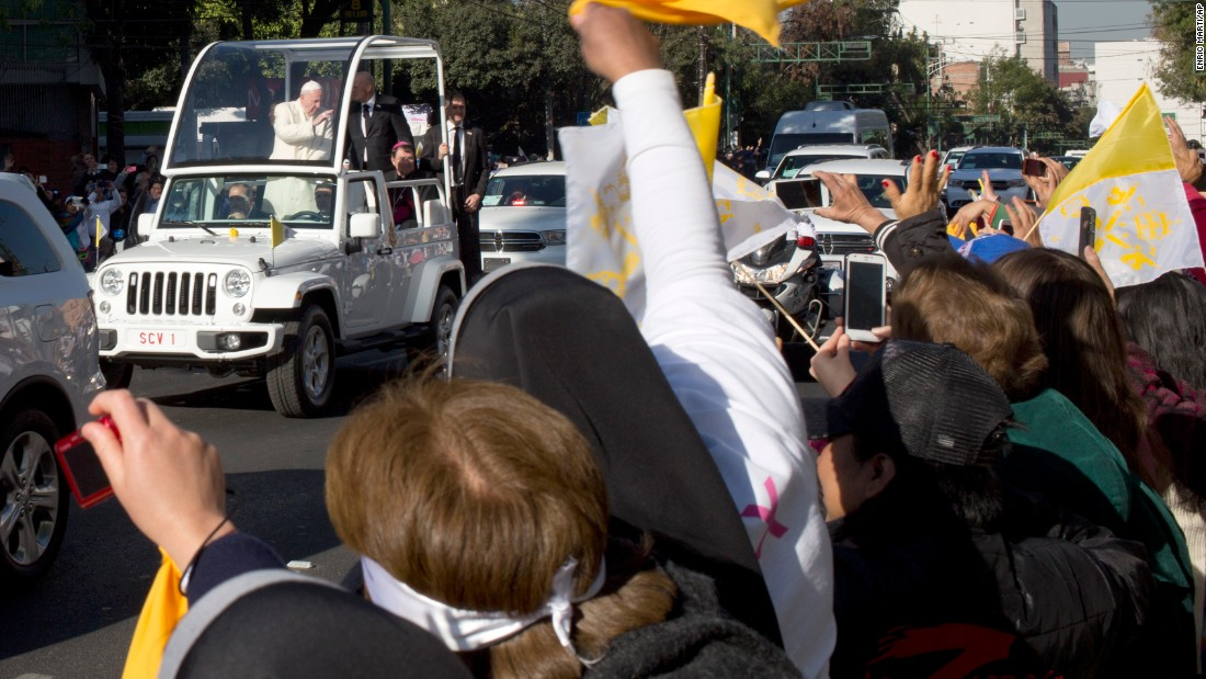 People wave to Pope Francis as he makes his way to Mexico City's main square.