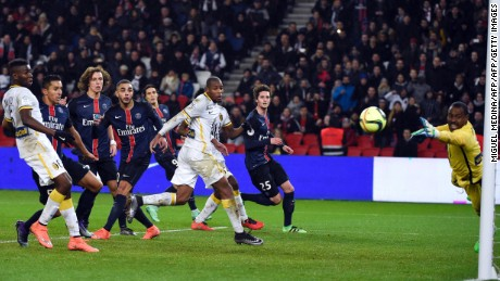 Lille's Nigerian goalkeeper Vincent Enyeama (R) dives for the ball as PSG players look on.