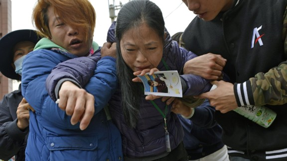 A mother holds a picture of her son after a male body was recovered on February 10.