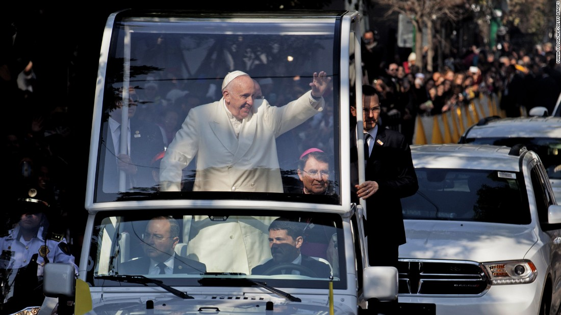 "Pope Francis waves from his ""Popemobile"" on his way to take a helicopter to Ecatepec."