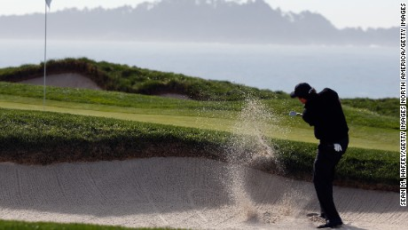 Mickelson plays out of the bunker on the fourth as he makes the first of two consecutive bogeys Sunday.