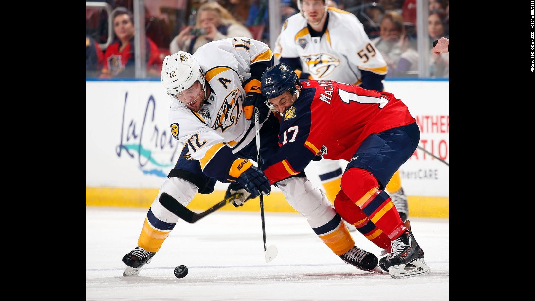 Nashville's Mike Fisher, left, competes for the puck with Florida's Derek MacKenzie during an NHL game in Sunrise, Florida, on Saturday, February 13.