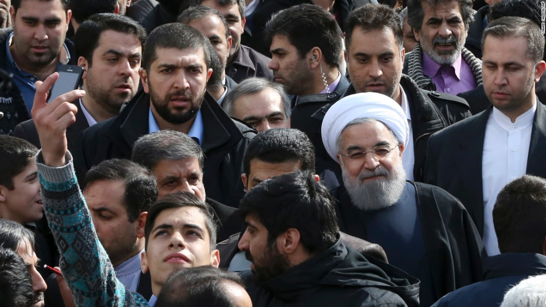 A man takes a selfie Thursday, February 11, as Iranian President Hassan Rouhani -- wearing the white turban -- attends a rally commemorating the anniversary of the Iranian revolution.