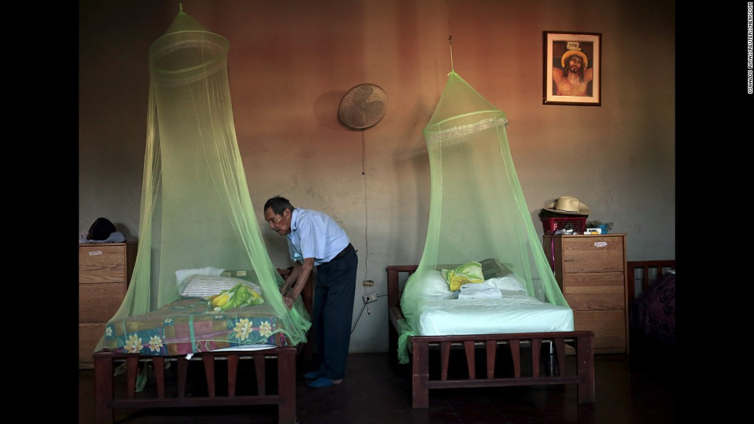 A man places a mosquito net over a bed at a home for the elderly in Masaya, Nicaragua, on Thursday, February 11.