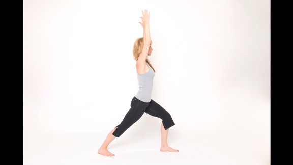 From standing, step your right leg back into a lunge but drop your heel all the way down and point your toes out slightly. Keep your back leg straight with your forward knee flexed to align above your ankle. Lift your arms overhead, shoulder-distance apart, keeping the shoulder blades stable down the back to maintain length in your neck.