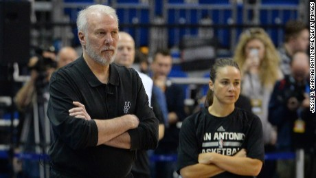 Spurs Head Coach Gregg Popovich and Becky Hammon watch over pregame warmups.