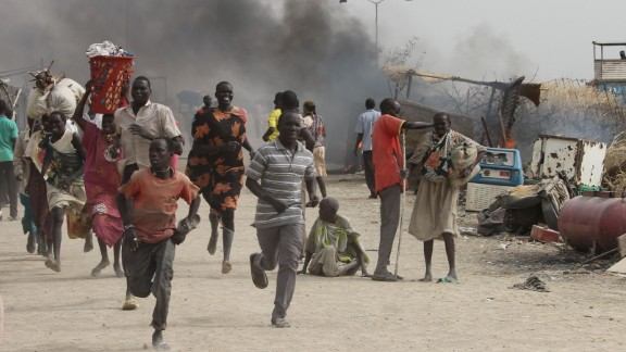 TOPSHOT - South Sudanese civilians flee fighting in an United Nations base in the northeastern town of Malakal on February 18, 2016, where gunmen opened fire on civilians sheltering inside killing at least five people.