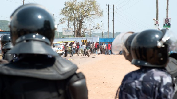 Riot police watch opposition supporters in a suburb of Kampala, Uganda, on February 18, 2016.
