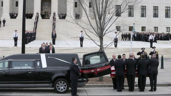 The pallbearers unload Scalia's casket from a hearse.