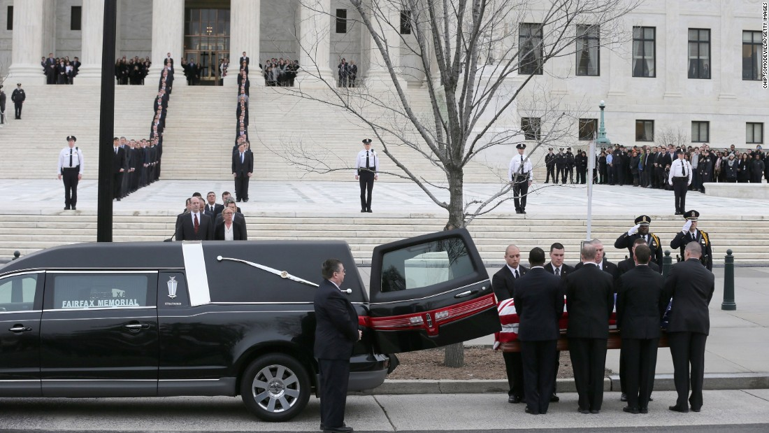 The pallbearers unload Scalia's casket from a hearse.