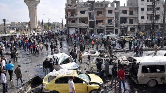 Syrians gather at the site of a double car bomb attack in the Al-Zahraa neighborhood of the Homs, Syria, on February 21, 2016. Multiple attacks in Homs and southern Damascus kill at least 122 and injure scores, according to the state-run SANA news agency. ISIS claimed responsibility.