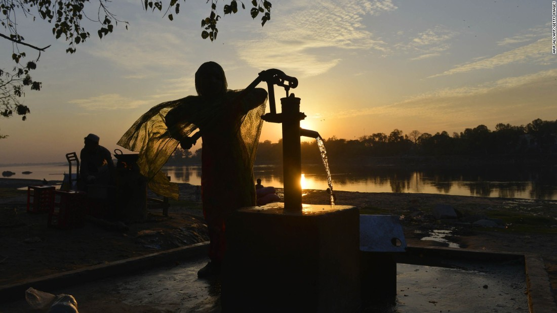 "A girl fills a can with water from a hand pump in a slum area of Lahore, Pakistan. ""More than 1 billion people without energy spend a significant portion of their time collecting wood and water for the basics of life,"" according to the Gateses."