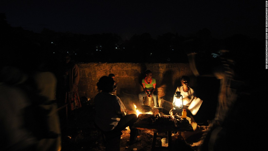 "Women cook by an open flame in a slum near Nairobi, Kenya. ""Without access to energy, the poor are stuck in the dark, denied all of the economic, social and health benefits that come with power,"" say the Gateses."