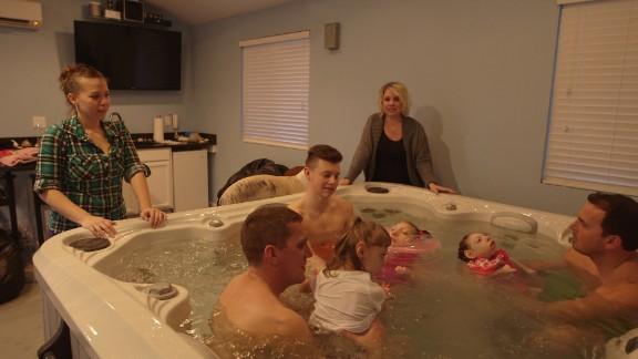 Angelina Aramburu and Gwen Hartley watch their families enjoy a hot tub.