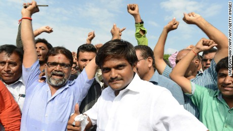 "Hardik Patel (C), an organiser of the Patidar community, gathers with group members for a rally demanding ""Other Backward Class"" (OBC) status in Ahmedabad on August 23, 2015. OBC members have urged the Gujarat government not to grant the Patel, or Patidar, community the status, which grants official protection of the members' social and educational development. AFP PHOTO / Sam PANTHAKY        (Photo credit should read SAM PANTHAKY/AFP/Getty Images)"