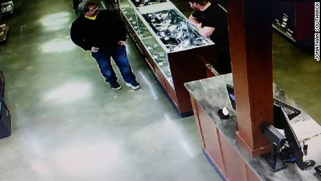 A surveillance photo shows the suspect in a gun store where he bought a jacket.