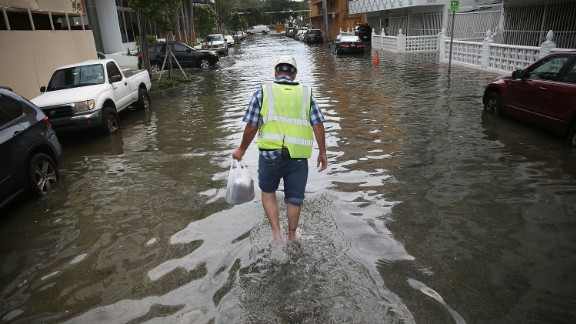 A Miami Beach resident walks through flooded streets in September 2015.