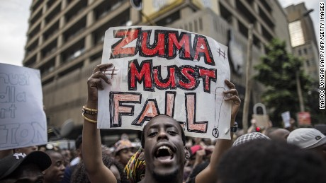 "A student holds a placard reading 'A placard with ""Zuma must fall"" outside the Luthuli House, the ANC headquarters, on October 22, 2015, in Johannesburg, during a demonstration of thousands of students against university fee hikes, in rolling protests that have become a focus for youth frustration in South Africa. AFP PHOTO / MARCO LONGARI        (Photo credit should read MARCO LONGARI/AFP/Getty Images)"