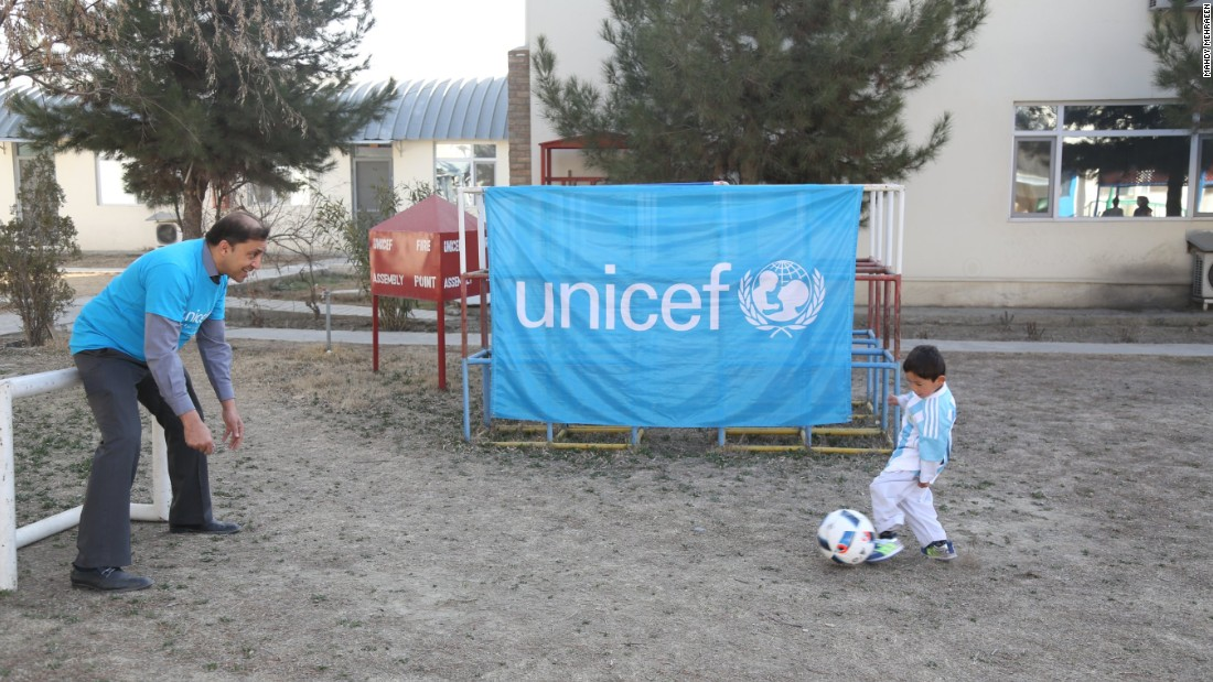 Murtaza dribbles as a UNICEF staffer takes on the role of goalkeeper.