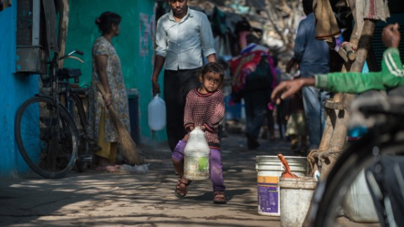 An Indian girl struggles to carry a jerry can filled with water as she helps family members fetch water from a distribution point in the low-income eastern New Delhi neighborhood of Sanjay camp on February 23, 2016. A water crisis in India