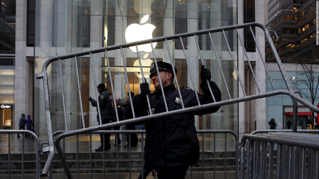 "A New York City police officer carries a steel barricade outside an Apple store on Tuesday, February 23. People gathered outside the store to protest the ruling that <a href=""http://money.cnn.com/2016/02/17/technology/fbi-apple-hack-iphone/index.html"" target=""_blank"">Apple must help the FBI</a> break into the phone of Syed Farook, one of the shooters in the December 2015 terrorist attack in San Bernardino, California. Apple has argued that coding a ""back door"" into the iPhone would compromise the security of hundreds of millions of its customers. The matter is now tied up in court, and <a href=""http://money.cnn.com/2016/02/24/news/companies/apple-tim-cook-abc-interview/index.html"" target=""_blank"">it has put Apple CEO Tim Cook in the spotlight</a> of a tense national debate about balancing security with privacy."