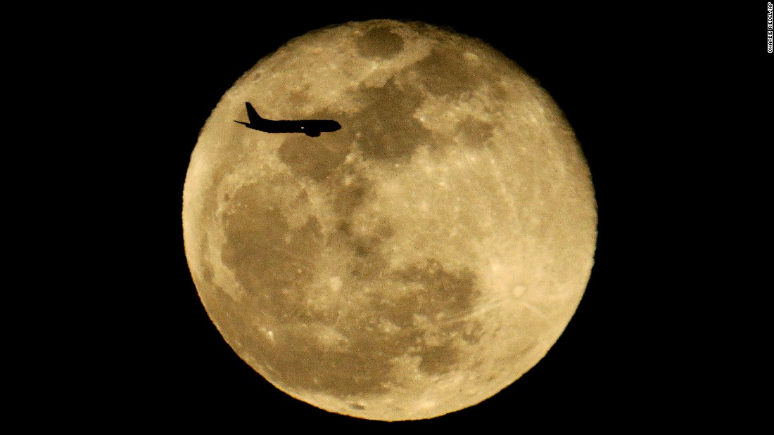 A passenger jet passes in front of a full moon as it approaches Phoenix's airport on Tuesday, February 23.