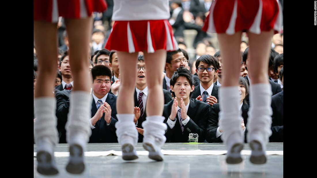 College graduates watch cheerleaders on stage during a job rally in downtown Tokyo on Thursday, February 25.
