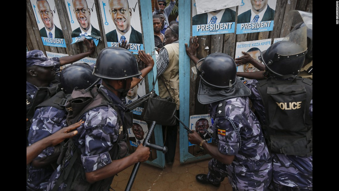 "Riot police officers in Kampala, Uganda, try to lock supporters of Kizza Besigye inside the presidential candidate's party headquarters on Friday, February 19. Police stormed the headquarters and put Besigye and six officials from his party under ""preventative arrest,"" they said. Authorities <a href=""http://www.cnn.com/2016/02/20/africa/uganda-election/"" target=""_blank"">detained the officials</a> because they planned to announce unauthorized results tallied by the opposition, police spokesman Patrick Onyango said. Under law, only election officials may announce results, he said. Preliminary figures showed Besigye had lost the election to incumbent Yoweri Museveni, but Besigye's party rejected the results and demanded an independent audit."