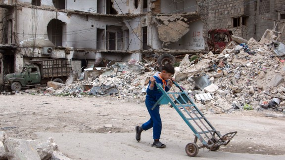 A boy walks a hand truck through a heavily damaged area in Aleppo.