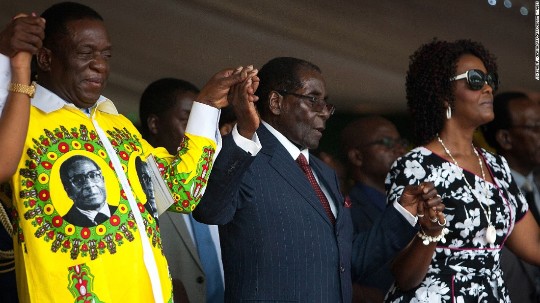 Zimbabwean President Robert Mugabe holds hands with Vice President Emmerson Mnangagwa and his wife during his birthday celebrations on February 27, 2016.
