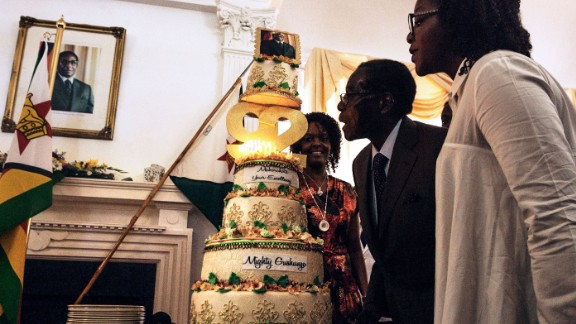 Zimbabwe President Robert Mugabe (C), flanked by his wife Grace Mugabe (L) and daughter Bona (R), blows out the candles on a cake celebrating his 92nd birthday.