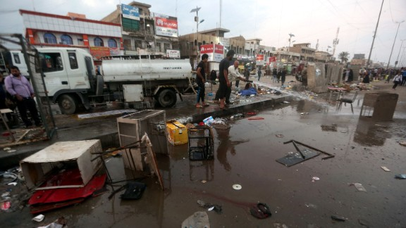 Men clean up the site of a bombing at a market in the Sadr City area of Baghdad Sunday. ISIS claimed responsibility for the attack.