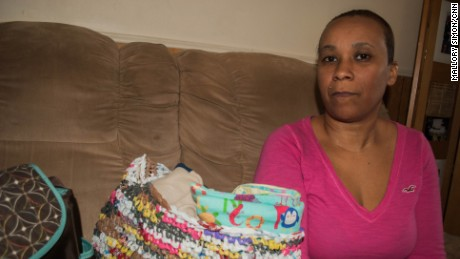 Nakiya Wakes sits with the clothes and supplies she bought in anticipation of a newborn baby.
