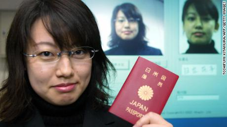 An employee of Hitachi demonstrates the new passport identify system developed by Hitachi and Glory Industry during a press preview at Hitachi's headquarters in Tokyo, 06 November 2003. The system can recognize one's identity even after the person has changed his/her hair-style, using glasses or even getting old.  Hitachi and Glory Industry will complete the new passport system until 2005 and are hoping to sell the identification system worldwide.
